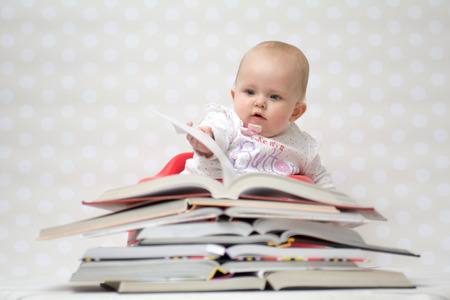 Prodigy: Cute baby girl sitting behind a pile of books Zdjęcie Seryjne