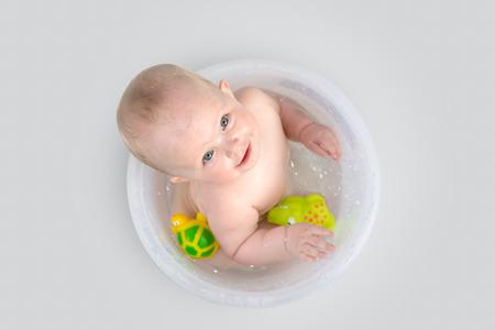 ba�andose: Los ojos azules de la ni�a en el cubo de ba�o mirando a la c�mara y sonriendo. Beb� feliz que tiene un ba�o y jugar con juguetes de goma. Foto de archivo