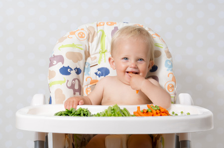Baby girl sitting in a highchair eating raw, seasonal vegetables: carrots, beans, peas, celery Banque d'images
