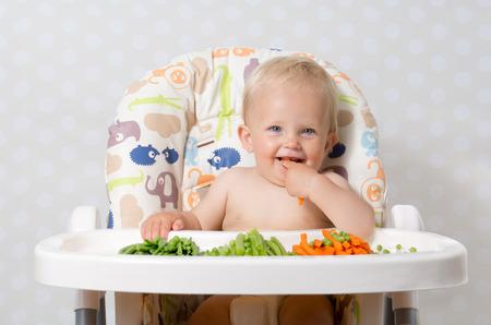 highchair: Baby girl sitting in a highchair eating raw, seasonal vegetables: carrots, beans, peas, celery Stock Photo