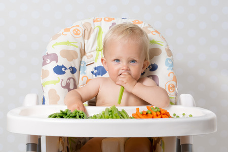 highchair: Baby girl sitting in a highchair eating raw, seasonal vegetables: carrots, beans, peas, celery Stock Photo