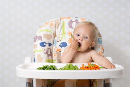 Baby girl sitting in a highchair eating raw, seasonal vegetables: carrots, beans, peas, celery Standard-Bild
