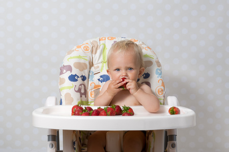 highchair: baby girl sitting in a highchair eating fresh strawberries Stock Photo