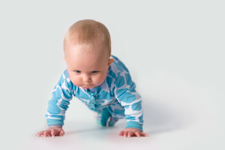 Baby in polka bleu pyjama se concentrer sur faire des push-ups Banque d'images