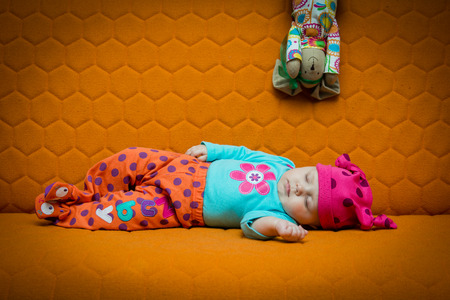 honey comb: Baby girl sleeping on an orange couch. Bright colors, dots, honey comb