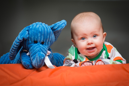 bald girl: Baby girl lying on a couch with her elephant friend looking at the camera Stock Photo