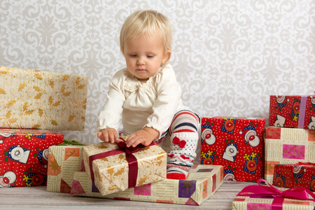 christmas shopping: An adorable baby girl concentrate when unwrapping Christmas gift