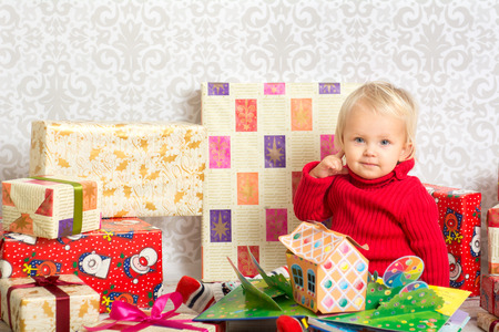festively: Dressed festively girl with stacks of present boxes around sitting on the floor and playing with paper gingerbread house. Stock Photo