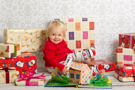 festively: Dressed festively girl with stacks of present boxes around sitting on the floor and smiling. Stock Photo