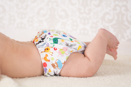 bald girl: Close-up on a reusable white nappy with colorful animals pattern