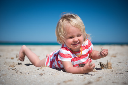 Happy girl lying on the sand and playing with sea plants and stones.