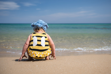 little girl wearing bee costume playing on the beach in the water. Summertime concept