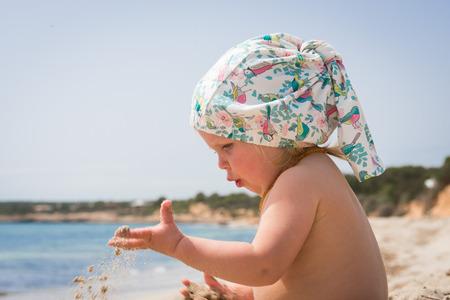 Little girl playing on the sandy beach near the sea