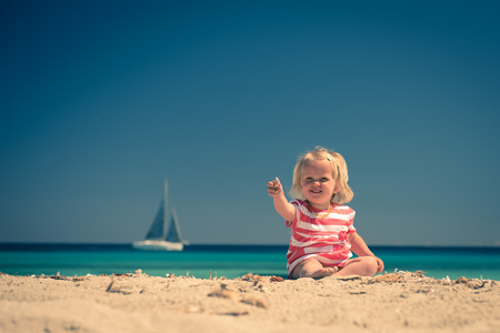 Adorable little girl sitting on  the beach and showing seashell.style toned