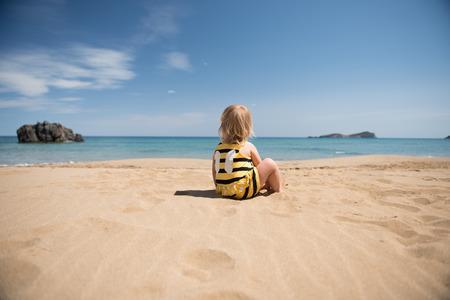 Petite fille assise sur la plage de sable et en regardant le concept horizon.Summer