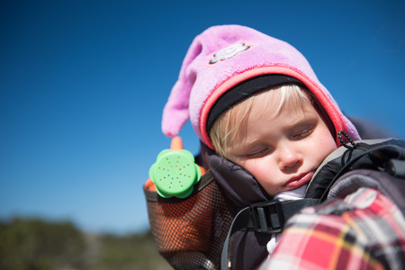 Portrait  of beautiful girl sleeping in carrier whilst  walking with her Father. Banque d'images