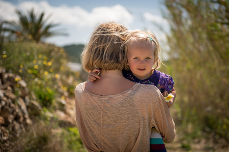 Little girl hugging embracing her mother and looking at the camera