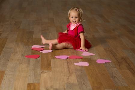 Fille habillée en rouge assise sur un plancher en bois avec le c?ur de beaucoup valentine autour et en regardant la caméra. Le concept de la Saint-Valentin