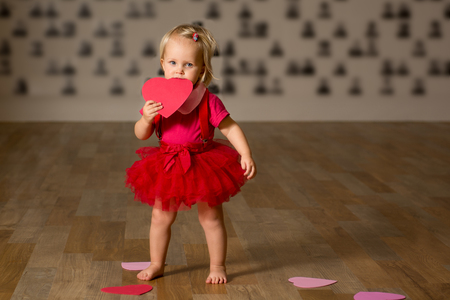 girl dressed in red bites valentines heart and looking at the camera. valentines day concept