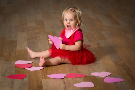 Excited sweet girl sitting on wooden floor and playing with hearts.