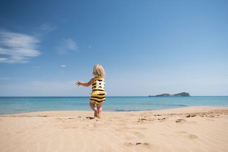 Bonne petite fille courir sur la plage en regardant la mer