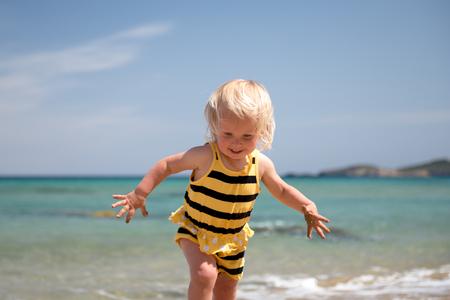 Mignon bébé amusant sur la plage jouer avec des vagues