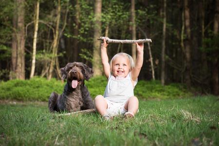 Petite fille avec son chien dans le bois sur une journée ensoleillée. Meilleur amis concept.Outdoor activité et jeu avec votre animal de compagnie sur les vacances d'été.
