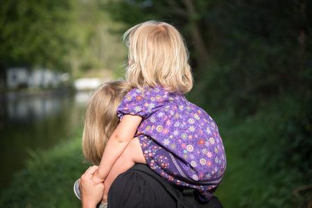 Portrait de tittle fille assise sur les épaules de sa mère marche dans le parc sur une journée ensoleillée au printemps avec le dos tourné.