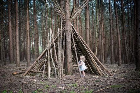 Petite fille jouant autour de la cabane dans le bois