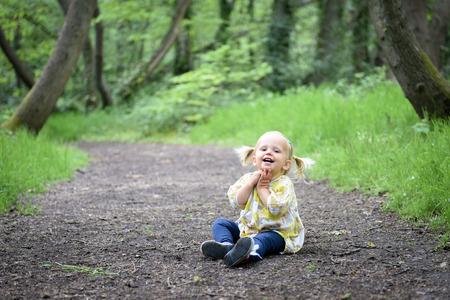 2 ans fille enfant en bas âge avec des queues amusant en bois Banque d'images