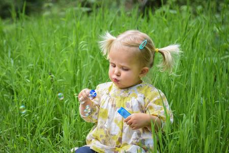 2 ans fille enfant en bas âge avec des queues assis sur l'herbe dans le parc de printemps soufflant des bulles de savon Banque d'images