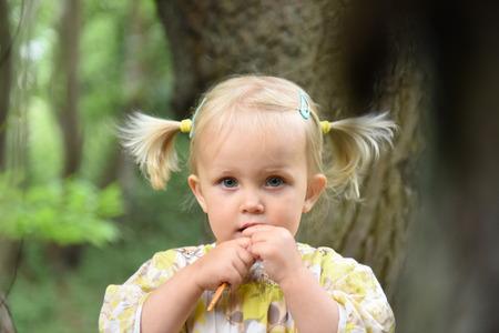 2 ans fille enfant en bas âge avec des queues et des yeux bleus regardant la caméra dans le parc Banque d'images
