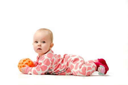 Petite fille portant pyjama blanc et rose, des chaussettes rouges joue avec sa balle orange en position couchée sur le ventre