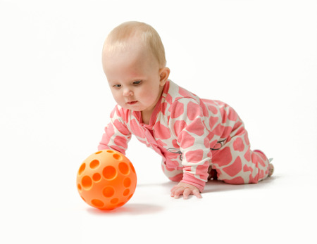 pyjama: Little girl wearing white and pink pyjama, red socks is playing with her orange ball while lying on a belly