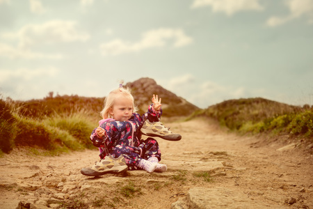 Petite fille est convenable sur les chaussures de la mère sur un chemin dans les collines.