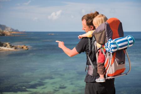 Père et fille dans le support de sac à dos en regardant vue panoramique. Voyage en famille Banque d'images