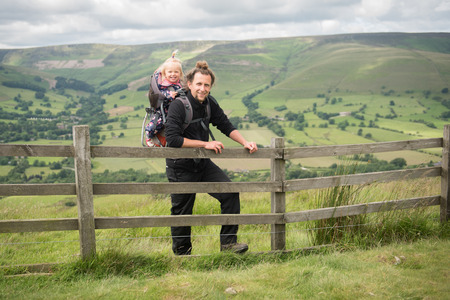 trecking: Happy young man enjoying  hiking with his little daughter in backpack child carrier