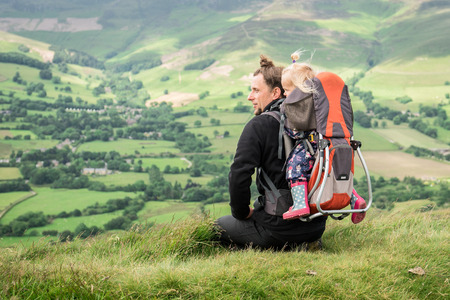 Young hiker with backpack child carrier and a baby girl inside, resting on the grass and looking at the beautiful landscape. Banque d'images