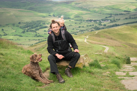 jeune randonneur heureux avec sa petite fille dans sac à dos porte-bébé et un chien, se reposer dans les montagnes.