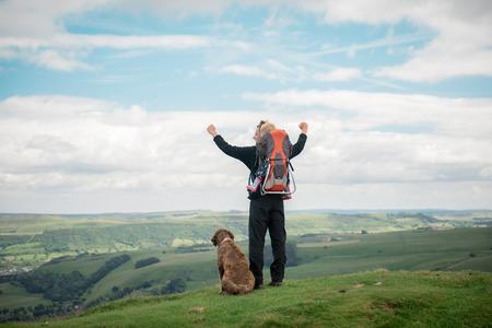 Jeune homme levant les mains et profiter de vue avec son chien et sa fille dans sac à dos porte-bébé Banque d'images