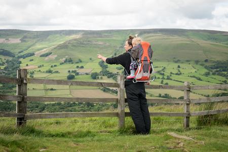 Jeune homme avec porte-sac à dos de l'enfant et une fille de bébé à l'intérieur du doigt pointant vers quelque chose dans le paysage