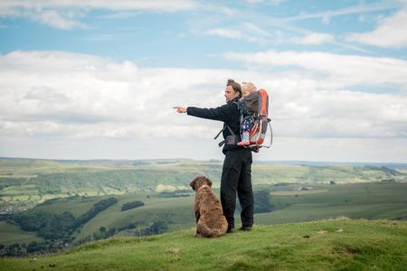 Un jeune père avec sa fille dans sac à dos porte-bébé et un chien de chien pointant du doigt quelque chose dans le paysage