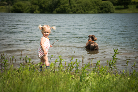 Happy little girl and her dog playing in the water in a beautiful countryside lake on a sunny summer day. Vacation concept.