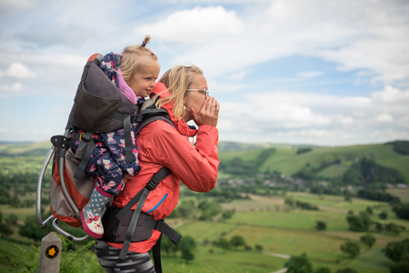 Young happy mother hold little traveler on back - baby girl in carrying backpack enjoying travel adventure, Hiking activity with child on family summer vacation, weekend nature tour Banque d'images
