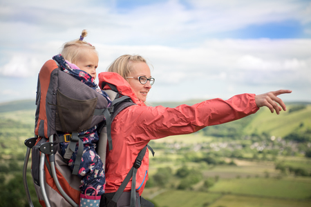 Happy young woman trekking with  baby in a baby carrier and her a dog, pointing at something in the landscape. Hiking activity with child on family summer vacation, weekend nature tour Banque d'images