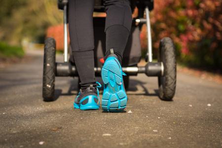 Mladá matka cvičí v parku. Nosí modrošedé sportovní boty, tlačí kočár