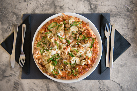 Closeup photo of a pizza meal in a restaurant on marble table and blue napkin