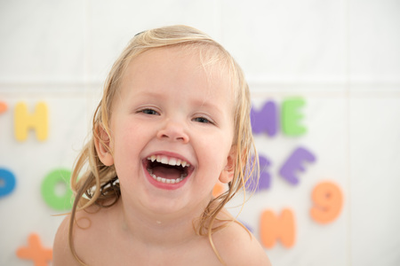 Cheerful little girl in bathroom with colorful foam letters and numbers in background. Beautiful wide smile of little girl with great healthy white teeth. Water fun for kids.