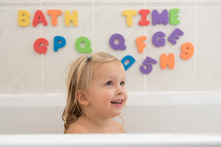 Smiling little girl in bathroom with colorful foam letters and numbers in background. Water fun for kids.
