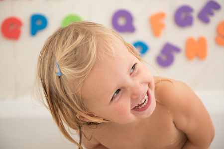 Smiling  girl in bathroom with colorful foam letters and numbers in background.Water fun for kids. Banque d'images